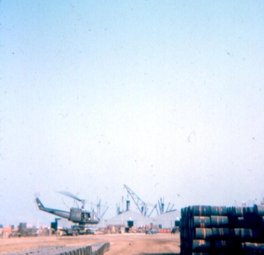 Chopper Taking Off From Satging Area Behind Warehouses At The  Docks - Look At All Those Agent Orange Barrels
