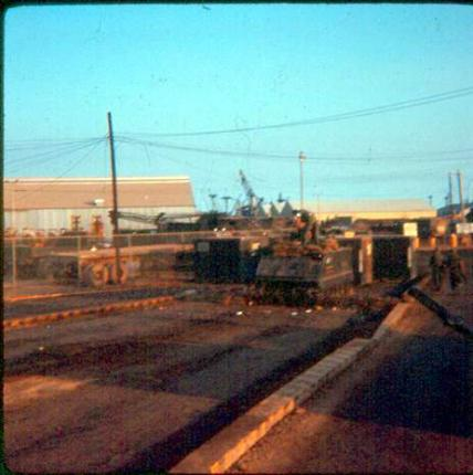 Morning Of February 2, 1968 - Security Guard APC Positioned At Newport Main Gate - MP's Positioned  Behind Sand Bags In Front Of APC -  Newport Maintenance Building Is In Left Background.