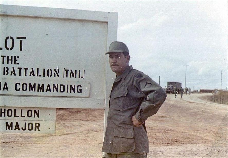 Armando Loya Standing Next To The Camp Camelot, 71st Transportation Battalion Sign