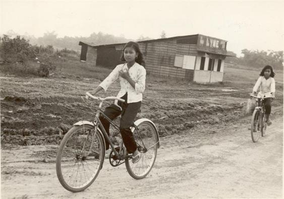 Two Young Vietnamese Girls Riding Their Bikes Up Bear Cat Road