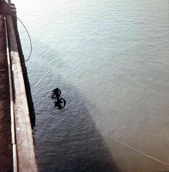 Navy divers inspect bombs underwater before bringing them up from sunken barge.