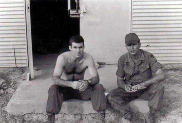 DeMininico and Jones are sitting outside the hootch at the 402nd company area.
